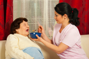 caregiver giving food to the elder woman