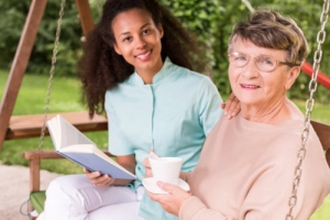 elderly woman holding a cup of coffee with her caregiver holding a book